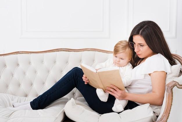 Madre leyendo en el sofá con bebé