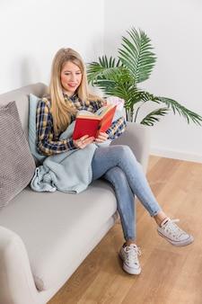 Madre con el libro de lectura del bebé en el sofá