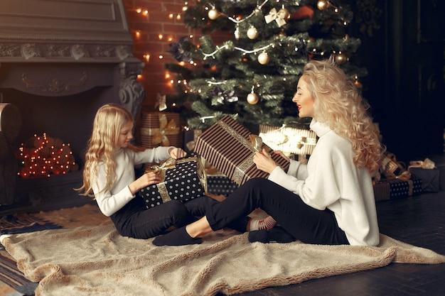 Madre con linda hija en casa cerca del árbol de navidad