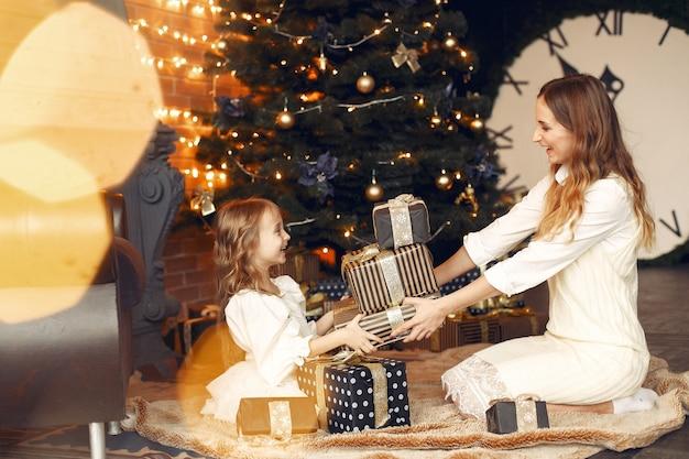 Madre con linda hija en casa junto a la chimenea