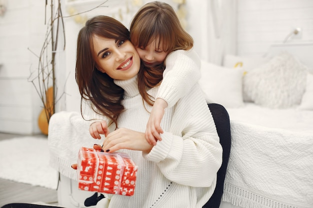 Madre con linda hija en casa con regalos de navidad