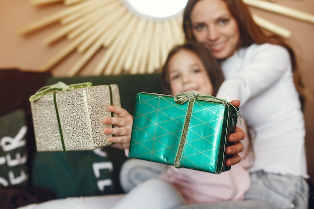 Madre con linda hija cerca del árbol de navidad