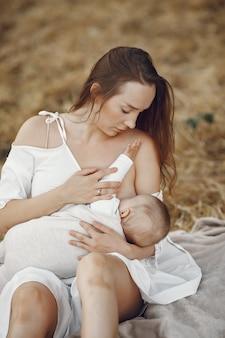 Madre con linda hija. mamá amamantando a su pequeña hija. mujer con un vestido blanco.