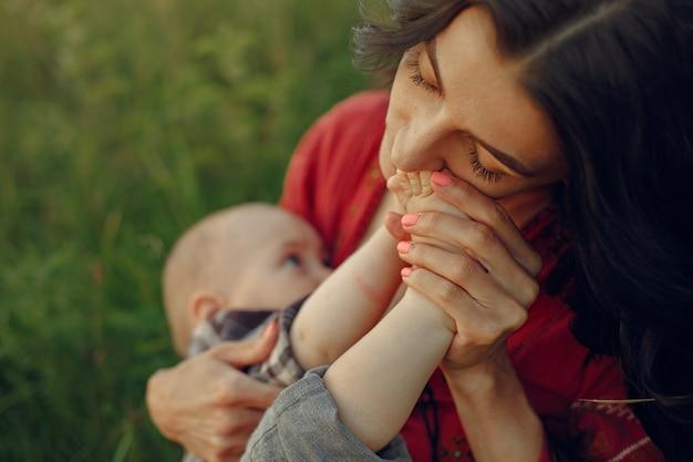 Madre con linda hija. mamá amamantando a su pequeño hijo. mujer con un vestido rojo.