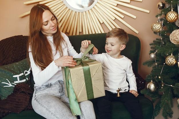 Madre con lindo hijo cerca del árbol de navidad