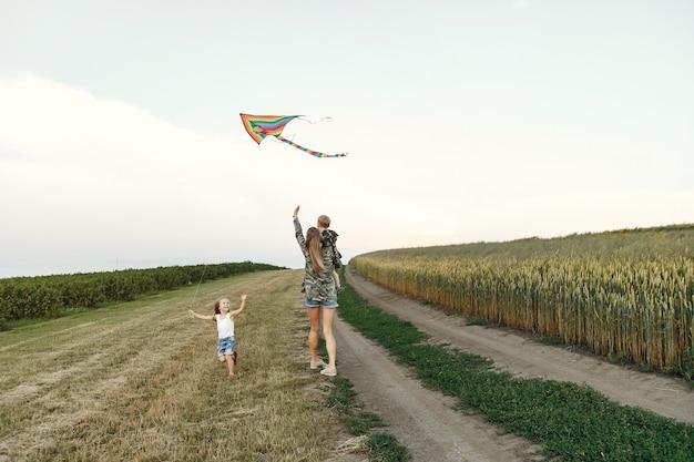 Madre con lindos niños pequeños en un campo de verano