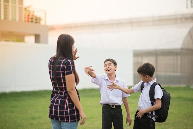 Madre llevando hijos a la escuela juntos, mano ola dice adiós