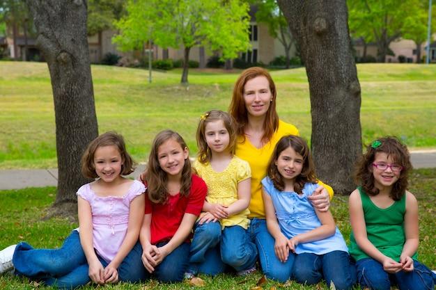 Madre maestra con hijas pupilas en parque infantil