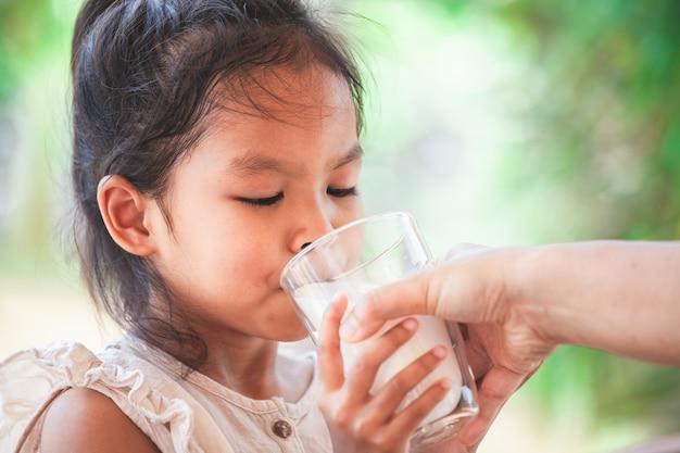 Madre mano dando un vaso de leche a su hijo con cuidado y amor.