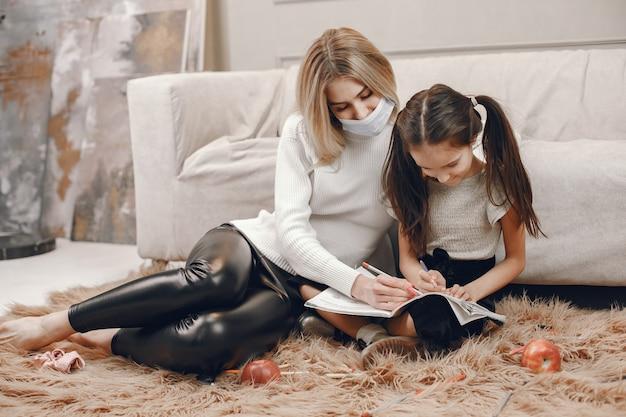 Madre en máscara con hija en el suelo. niña para colorear y madre ayudándola.