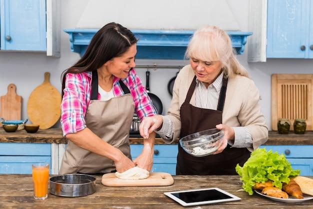 Madre mayor alegre que ayuda a su hija para amasar la pasta