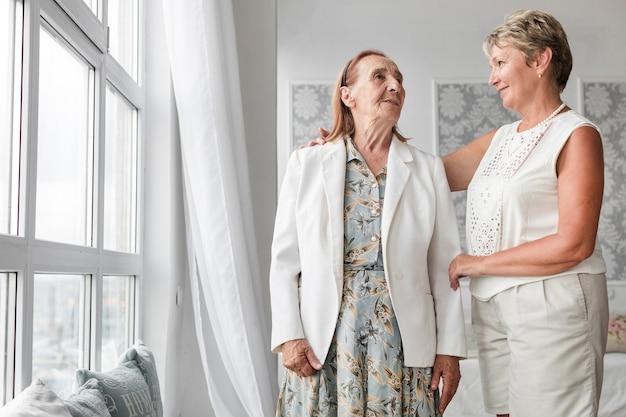 Madre mayor e hija que se miran mientras que se coloca cerca de ventana