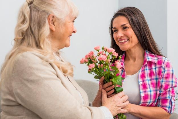 Madre mayor sonriente y su hija que sostienen el ramo color de rosa