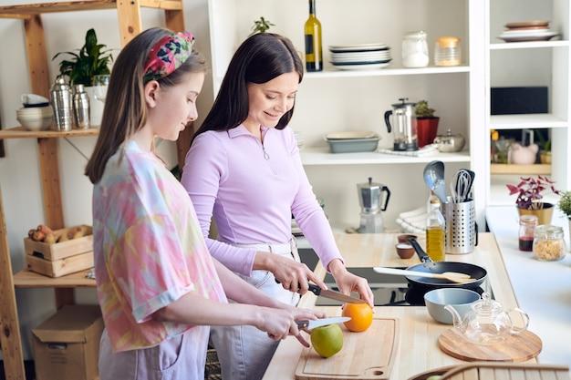 Madre de mediana edad positiva y su hija adolescente de pie en el mostrador de la cocina y cortando frutas mientras preparan el desayuno juntos
