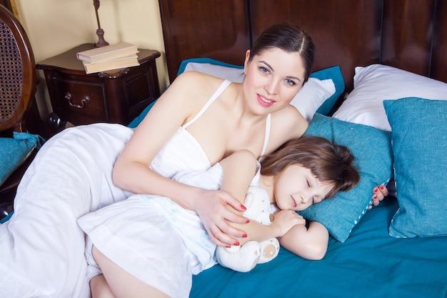 Madre mirando a la cámara con una sonrisa dentuda y su hija durmiendo cerca. tiro del estudio