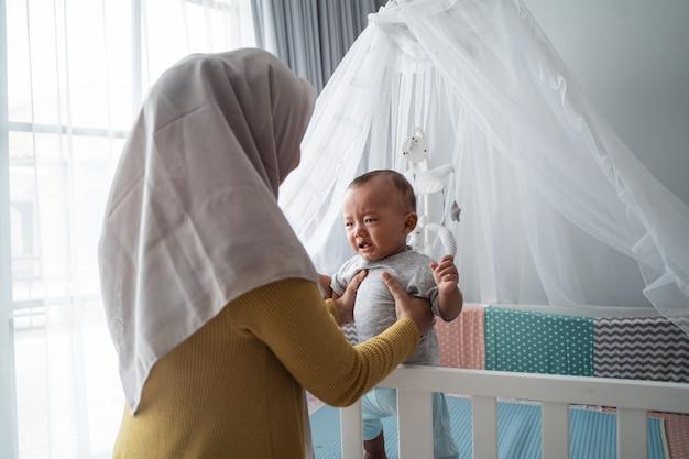 Madre mirando a su bebé llorando
