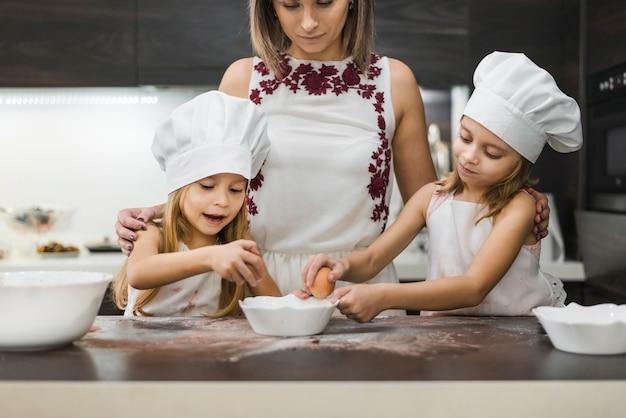 Madre mirando a sus hijas rompiendo huevos en un tazón