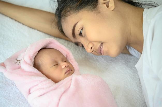 Madre miró al bebé recién nacido en la cama