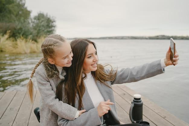 Madre de moda con hija. gente de picnic. mujer con un abrigo gris. familia junto al agua.