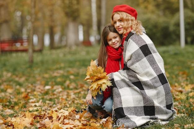 Madre de moda con hija. otoño amarillo. mujer con pañuelo rojo.