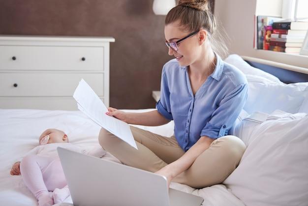 Madre moderna trabajando mientras su hijo duerme