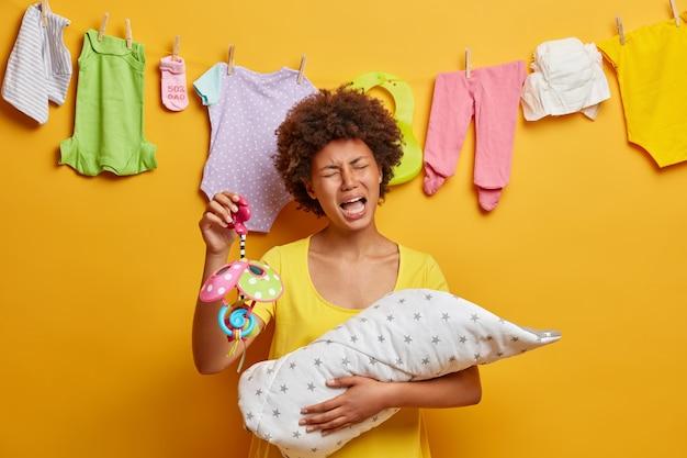 Madre molesta disgustada que está cansada de amamantar al bebé, sostiene el móvil, intenta calmar el llanto del recién nacido, ocupada con las tareas domésticas y el cuidado de niños, posa