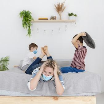 Madre molesta con máscara médica y niños peleando con almohadas