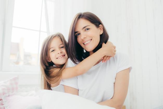Madre morena guapa con suave sonrisa y su pequeña hija da un abrazo