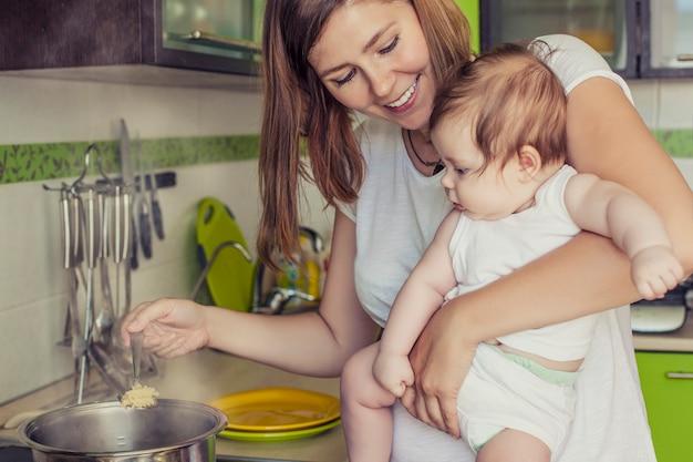 La madre de una mujer con un bebé cocina la comida en una olla en la estufa