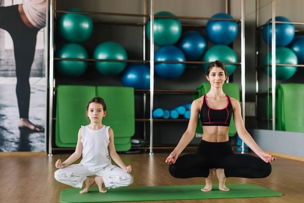 Madre y mujer haciendo yoga juntos en el gimnasio
