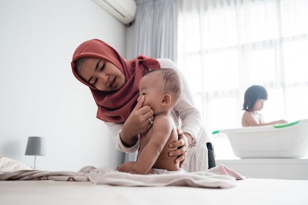 Madre musulmana limpia su cara de bebé