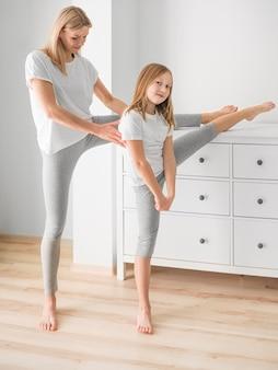 Madre y niña en casa estirando