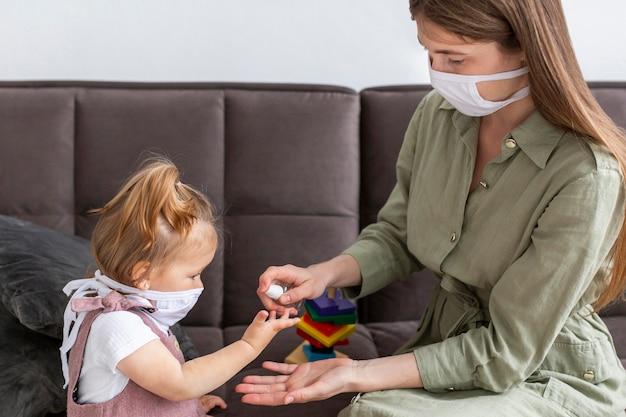 Madre y niña desinfectando las manos