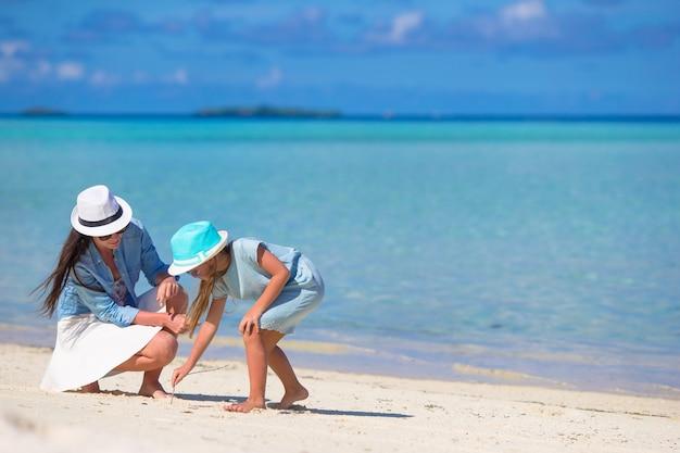 Madre y niña de dibujo en la playa de arena