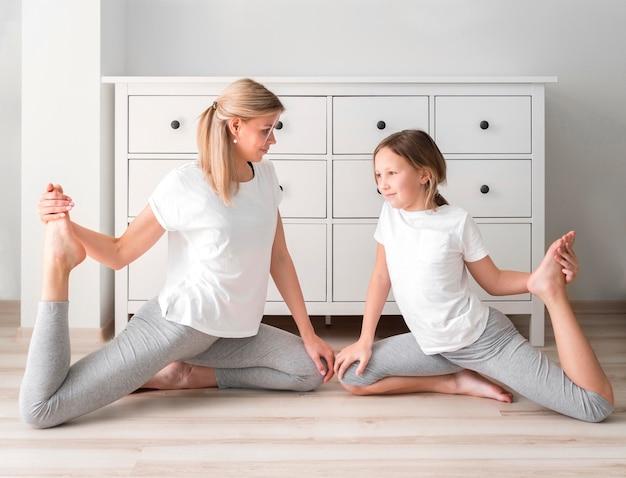 Madre y niña entrenamiento deportivo en casa
