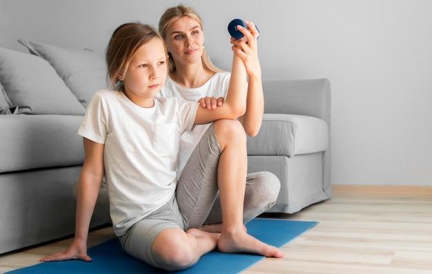 Madre y niña entrenando con pesas