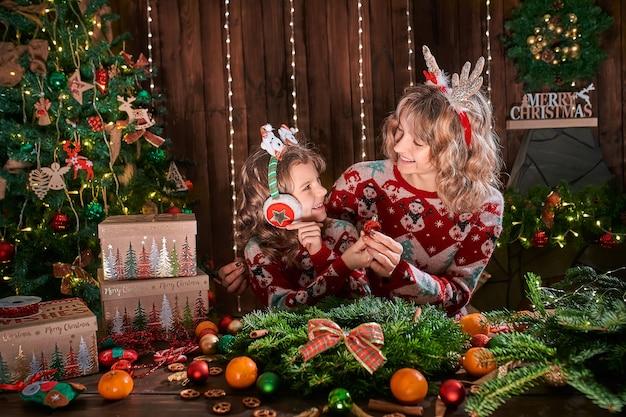 Madre con niña niño cerca del árbol de navidad.