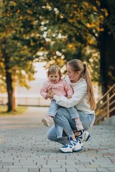 Madre con niña en parque otoñal