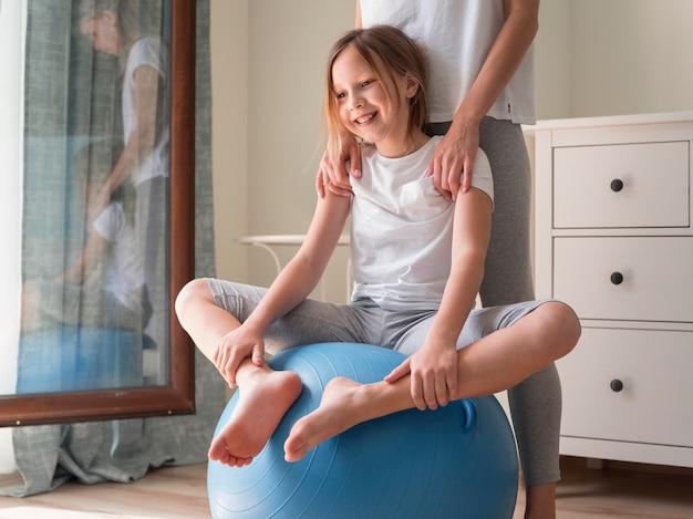 La madre y la niña practican deporte en pelota