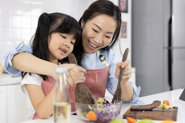 Madre y niña preparan la ensalada en un bol