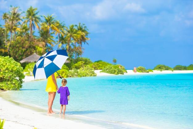 Madre y niña con sombrilla escondiéndose del sol en la playa