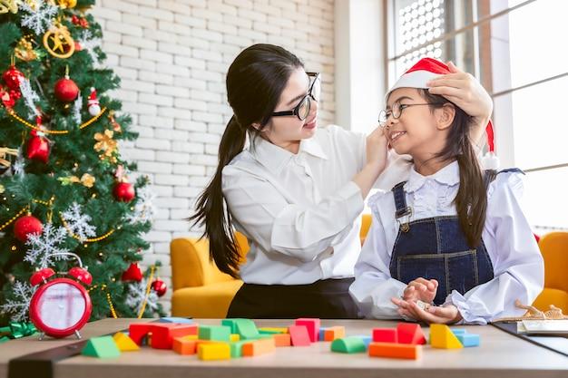 Madre y niña sonriendo y jugando juguete en navidad.