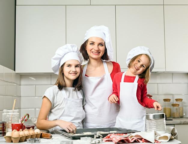 Madre con niñas preparar masa para hornear