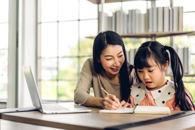 Madre y niño asiático niña aprendiendo y mirando la computadora portátil haciendo la tarea estudiando conocimiento con el sistema de e-learning de educación en línea