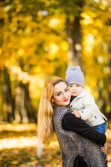La madre y el niño caminan en el parque de otoño dorado.