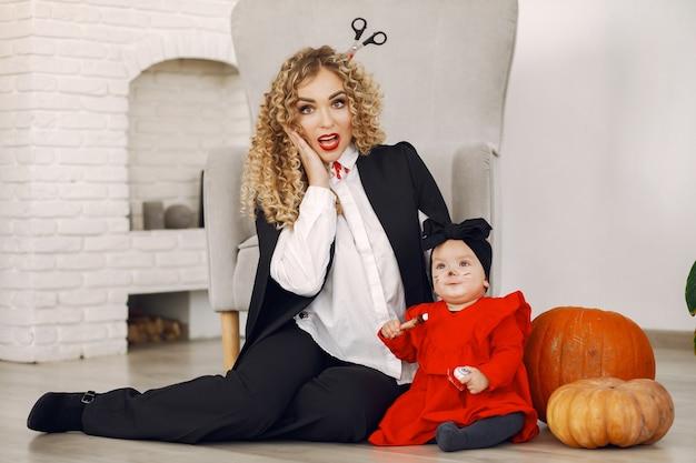 Madre con niño en disfraces y maquillaje. la familia se prepara para la celebración de halloween.