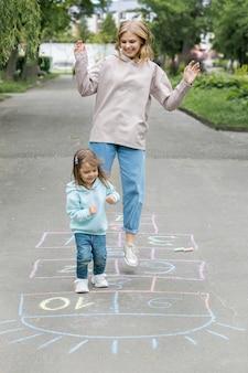 Madre y niño lindo jugando a la rayuela
