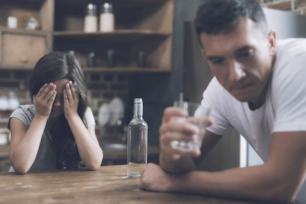 La madre y el niño miran al padre borracho en la cocina