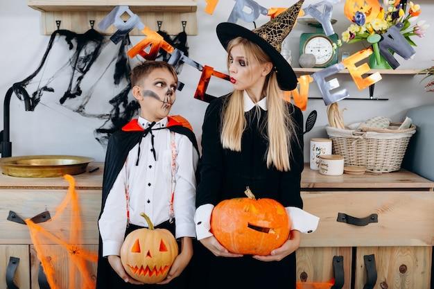 Madre y niño de pie en traje de mascarada sosteniendo una calabaza y mirándose