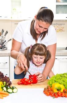 Madre y niño preparando comida sana.